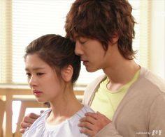 """Ha Ni trata de explicarle sin éxito a Seung Jo lo del rumor. Va a su casa para hablar con él, pero se encuentra con un enfermo Eun Jo. Por teléfono Seung Jo le indica como auxiliarlo. Luego, una nerviosa Ha Ni se retira del cuarto de Eun Jo, pero Seung Jo la toma del hombro y la detiene: """"El rumor sobre Kyung Soo..."""", él se acerca más tomándola de los hombros: """"Ya me lo explicó""""- acercándose tiernamente- """"Gracias"""". Ella explota en llanto y él la recibe en sus brazos - Playful Kiss, Episodio…"""