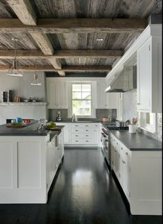 Dark floors work well and offset by white cabinets and a beautiful and organic wood ceiling with thick beams