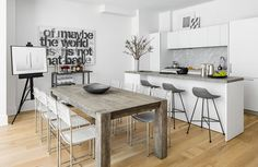 Open-plan kitchen with a dining space, an island, gray barstools, and white cabinents with marble backsplash