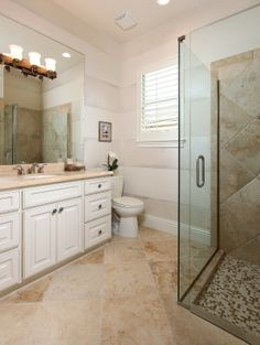 Third bath with glass shower and custom tile flooring.