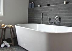 """Wem """"ganz in Grau"""" zu viel ist, der sollte es zunächst mit einer einzelnen grauen Wand versuchen. Die kann dann auch ruhig etwas dunkler ausfallen, wird sie doch durch umgebendes Weiß in der Wirkung gemildert. Passende graue Fliesen sind zurzeit in allen möglichen Formaten erhältlich – von Mosaik bis Großformat. Ein rustikaler Hocker und die flauschige Ton-in-Ton-Badematte bringen Wohnlichkeit ins zeitlose Bad. Foto: freshideen.com"""