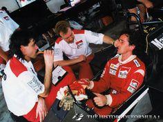 Alain Prost describes the behaviour of his McLaren with designer Gordon Murray (left) and engineer Neil Oatley. The bodywork has been removed.