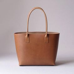 [About item] This bag made with hand stitched of thick vegetable tanning leather and hemp thread, the simple tote bag independent tightly. You can also put over shoulders. The roundish handle. [specs] Leather: Vegetable tanning leather (Italy or Japan) Sewing: Full hand stitched Edge: Hand