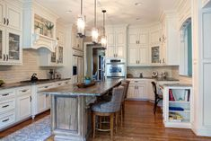 The Classic Style perimeter cabinets are a Off White with a thin Toasted wheat glaze. The kitchen island  is wormy maple with our custom stain called Ipswitch Pine with a Raw Umber Glaze. #white #kitchen #cabinets