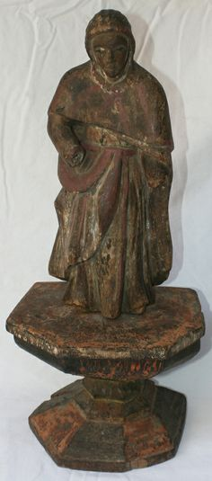 Antique wooden Filipino Santos statues are carved and painted saint statues of Christian saints, angles, or other religious figures. This Santos is of a cloaked and hooded woman, standing (secured) on a large pedestal. Possibly representing Saint Anna, the sister of the Virgin Mary, and mother of John the Baptist. She is missing her removable hands-a fate not uncommon for older Santos. The finish is a lovely patina of browns, reds and natural hues.  http://www.silkroadcollection.com