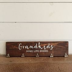 Grandkids Make Life Grand Wood Photo Sign | Picture Display | Home Décor | Christmas Gift  PRODUCT DESCRIPTION: Grandkids Make Life Grand Wood Photo Sign. The perfect gift for any Grandparent! Hooks are included for hanging. Each order is custom made and hand painted, so some variation should be expected. SIZE & MATERIAL: Approx. 7x 24 5 photo hooks  White paint on dark stained wood… Have something else in mind? Message us to customize any order!  SHIPPING: We ship all of our items via USPS…