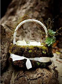A flower girl basket is covered with moss and succulent accents and filled with white petals.