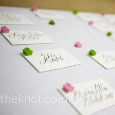 The couple painted Monopoly game pieces green and pink and placed one house on each envelope to punch up the escort card display.  from the album: An Outdoor Wedding in Fort Lauderdale, FL