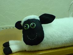 Here's my version of a sheep draught excluder, made for a friend with a draughty door.A fur fabric body and felt head and a loop on his back to help pick him up.