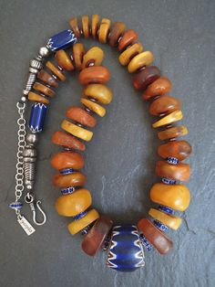 by Luda Hunter / GEMILA Jewels | Necklace; antique Moroccan natural fossil amber beads, huge old 6 layer Chevron African Trade bead, combined with chevron spacer beads, finished off with Indian tribal siver cone beads and sterling silver chain | 2'885 $Au