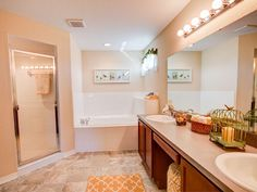 Dual vanities, seated vanity space, a fully-tiled shower and relaxing garden tub complete this luxury master bathroom. Highland Homes' Remington IV model home in Ocala, Florida.