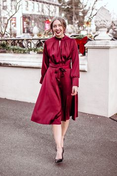 Classy holiday party outfit in a red satin dress, a low bun, black pumps, and red festive earrings.  Red dress for the holidays, holiday dress, classy Christmas dress, classy Christmas party outfit, classy Christmas outfit.  See 10 other holiday party or Christmas party outfit ideas in this blog post.
