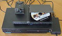 Comparación de la Playstation 2 original gruesa (Fat) con la versión delgada (Slim), con una cámara Eye Toy conectada al puerto USB.