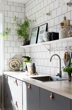 Sunny, artful and green kitchen. Love the decor and natural look in this space.