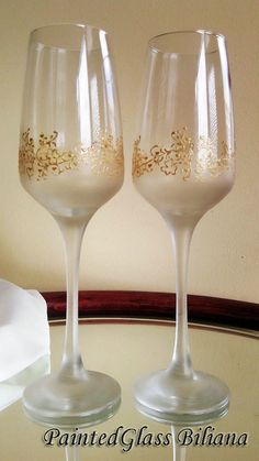 Set of 2 hand painted toasting champagne flutes with very delicate golden lace with clovers and small hearts around the glass and golden