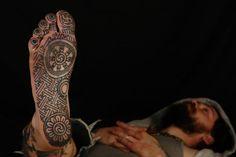 tatouage homme plante de pied avec swastika hindou