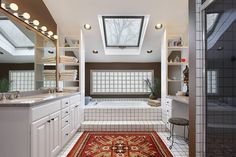 Sharply contrasting bathroom in white tile features a large soaking tub beneath skylight, nestled between a dual vanity at left and makeup desk at right. Bold color patterned rug ties the space together at center.