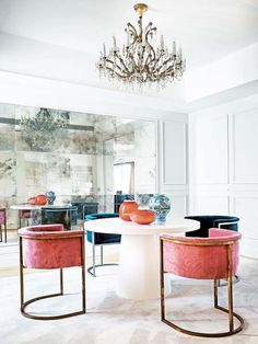 Glamorous dining room with pink velvet dining chairs and mirrored wall
