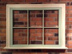 Old vintage wooden window repurposed to be the focal piece over a fireplace. Repainted and trimmed out.