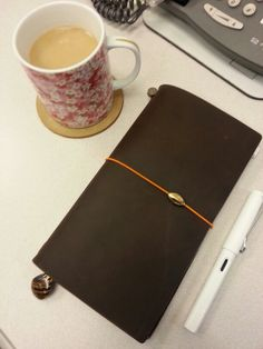 These are a few of my favorite things: Sakura coffee cup, Midori Traveler's Brown Notebook (which arrived last week!!) and white Lamy Safari fountain pen.