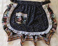 An adorable upcycled denim half apron with lacy ruffles, buttons, and lace trim is a fashion must! The original waistband buttons in back fits a 33 waist or hips depending on where you position this fun number. Two front pockets are embellished with trim and buttons and easily hold phone or keys.  Just a little country kitchen lingerie.  Handmade with love in Colorado.