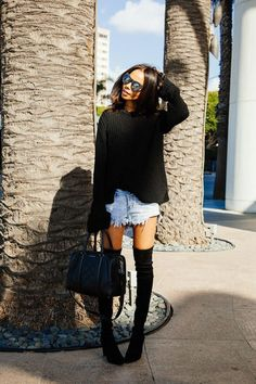 A black oversized sweater and baby blue denim shorts are a great outfit formula to have in your arsenal. Black suede thigh high boots will instantly smarten up even the laziest of looks. Shop this look for $91: http://lookastic.com/women/looks/black-oversized-sweater-light-blue-shorts-black-duffle-bag-black-over-the-knee-boots/4637 — Black Oversized Sweater — Light Blue Denim Shorts — Black Leather Duffle Bag — Black Suede Over The Knee Boots