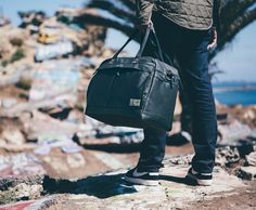 "Calibre Black Overnight Travel Bag in Matte Black.  Includes roomy main compartment for plenty of clothing, 2 front pockets: one faux fur lined and padded for tablets and e-readers, and the other contains an organizer and room for phone, chargers, or accessories. The rear side of the bag boast a large padded exterior access pocket for your 13""-15"" Macbook Pro or other similar sized laptop. Constructed from water resistant, heavy matte coated canvas with copper colored hardware."