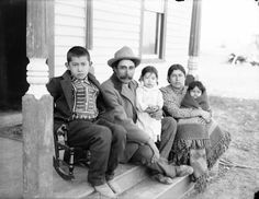Packineau, Joe and Family, Elbowoods. 	[1902] View of man and woman with two children and an infant seated on porch. Boy sits on small rocker. Man, wearing hat and coat, holds girl. Woman, wearing cloth dress, holds infant wrapped in blanket. Photographer: L. A. Huffman. Catalog #: 981-218; Vintage negative #number: 45.