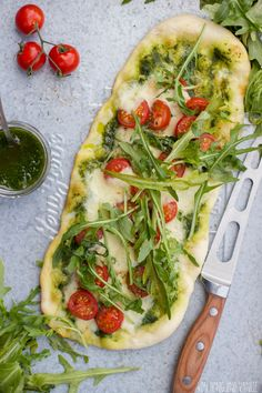 Pizza with basil pesto, tomatos, mozzarella and arugula