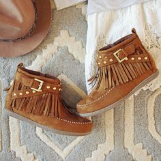 Sweet studded & fringe details adorn these darling moccasins. A dark chestnut brown has been designed with a sweet gold buckle and studded upper, fringe & stitch details, and a rubber sole. Side zipper for easy on and off wear. The sweetest moccasins for the season.  Color: Chestnut brown Man made materials
