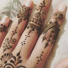 Intricate henna design on the fingers