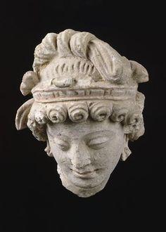 Tête de Devata (C) RMN-Grand Palais (musée Guimet, Paris) / Daniel Arnaudet 3e siècle, 4e siècle stuc Afghanistan, monastère de Hadda