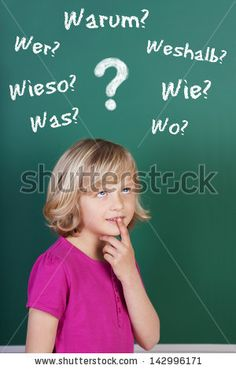 Young blond schoolgirl full of doubts thinking in front of the blackboard in the classroom - stock photo