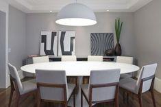 Sala de jantar com mesa oval branca Saarinen + cadeiras de madeira e tecido claro + pendente redondo branco + aparador de laca com quadros apoiados. Gosto muito da cor cinza das paredes contrastando com o rodapé branco mais alto.: