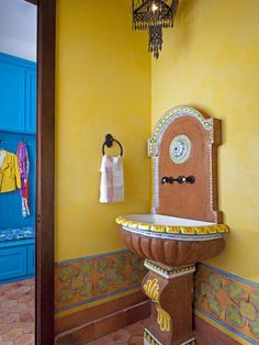 The Powder Room off a Mud Room in this Spanish style home utilizes a colorfully painted old wall fountain for the sink...