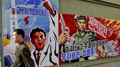 FILE - In this March 26, 2013 file photo, a North Korean man walks past propaganda posters in Pyongyang, North Korea, that threaten punishme...