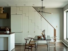 In Prospect Park home in Brooklyn, Workstead designed an open kitchen and dining room space with custom cabinets that zigzag their way up the stairs. For the dining area, they used different colored Hans Wegner Wishbone chairs with an industrial chandelier they designed and sell themselves.