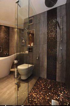 salle de bain de luxe décorée d'une mosaïque dorée et un carrelage mural aspect béton