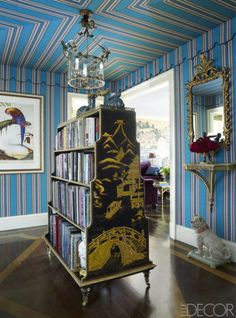 In a nod to the postwar French decorator Georges Geffroy, Alex Papachristidis sheathed the entrance hall of his New York City apartment with a Lee Jofa variegated-stripe linen, mitering the corners and adding a scalloped valance to evoke a campaign tent. A vintage tole light fixture, an antique bookcase, and a print by Walton Ford enhance the room's exotic appeal.