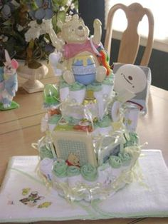 Charming...simply charming! This darling Winnie the Pooh diaper cake has such a whimsical feel to it. The colors used and the ceramic Pooh piggy bank is