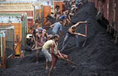Indian laborers load coal onto trucks at a coal depot on the outskirts of Jammu, India, on August 23, 2012. (AP Photo/Channi Anand)