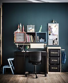 A child's workspace with lots of storage in front of a dark wall.