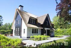 Witte rietgedekte villa met natuursteen trasraam houten accenten en schoorsteen te Blaricum