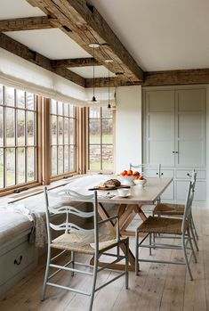 The eat-in dining space in the kitchen is where most meals are enjoyed. Farmhouse-style chairs in a dreamy blue-gray shade are by David Iatesta, and the pendants are antique.