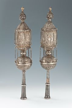 "A LARGE PAIR OF SILVER TORAH FINIALS. Persia, c. 1900. On long slaves that connect to a spherical midsection which attaches to an upper hexagonal body. Decorated with chains and engraved with Hebrew. 14.7"" tall."