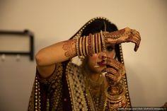 Traditional Indian wedding, bride wearing burgundy and gold lehenga and jewelry, and showcasing beautiful henna / mehndi.