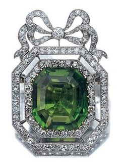 Peridot and Diamond Brooch, circa 1910. Mounted in platinum, centring one octagonal-cut peridot, approximately 18.00 cts, framed by 2 rows of 77 old-mine cut diamonds, topped by a diamond-set bow, altogether 118 diamonds, approximately 3.00 cts.