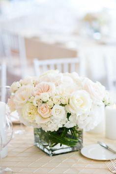 Low clear cylinder vases with curly willow tips looped in the base filled with cream hydrangeas, dusty blush roses, and ivory roses; surrounded by stemmed clear votives and low fluted votives