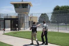 White House is pushing to aid more than inmates in being released. {A police officer and a correctional officer patrol the entrance of the El Reno Federal Correctional Institution in El Reno, Oklahoma.