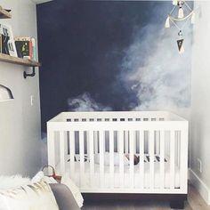cloudy sky mural behind crib